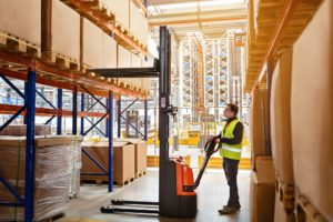 Employee working on warehouse with boxes on shelves. Worker operator using reach truck
