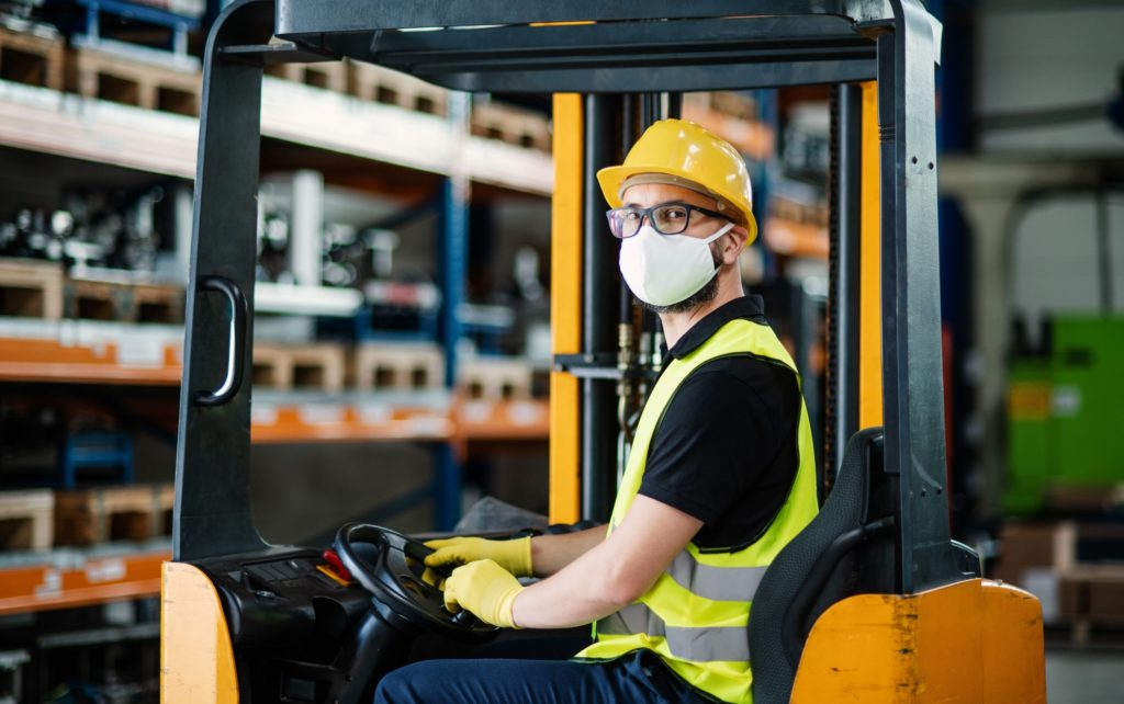 Man worker forklift driver with protective mask working in industrial factory or warehouse