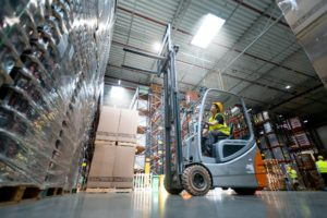 Warehouse worker operates a forklift